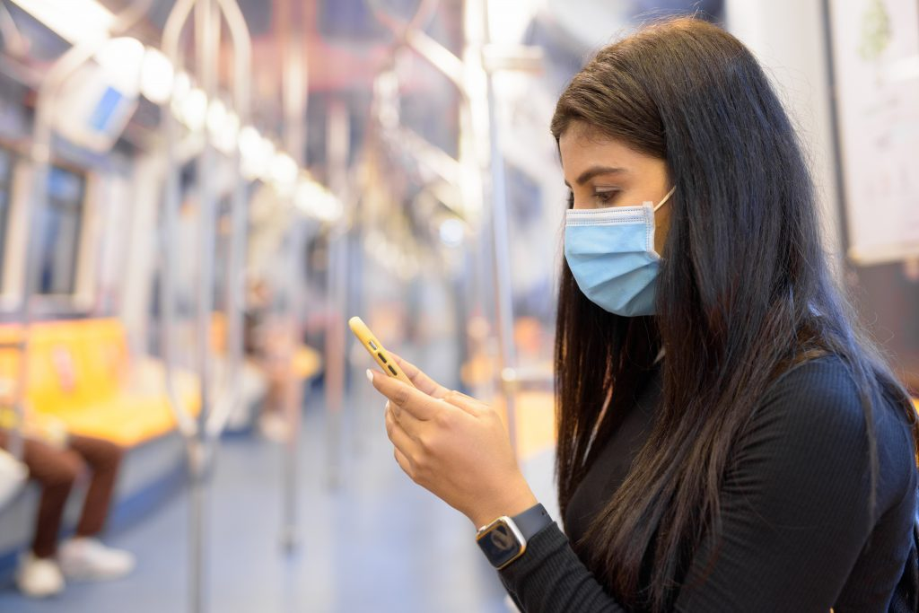 Young Indian woman with mask using phone and sitting with distance inside the train